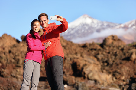 Couple taking selfie hiking in beautiful nature with smart phone. Happy couple walking enjoying view and taking pictures with smartphone. Man and woman by Volcano Teide on Tenerife, Canary Islands. photo
