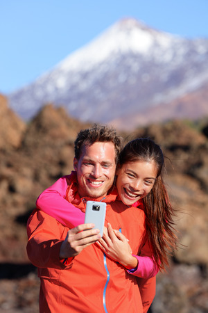 Selfie couple hiking in beautiful nature with smartphone. Happy couple walking enjoying view and taking pictures with smart phone. Man and woman by Volcano Teide on Tenerife, Canary Islands. photo