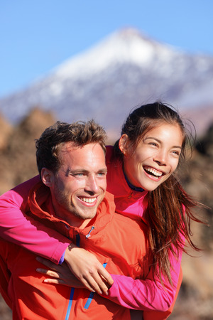 Happy couple piggyback in active lifestyle having fun on hike. Fresh young joyful interracial couple. Asian woman hiker and Caucasian man in outdoor activity on Teide, Tenerife, Canary Islands, Spain photo