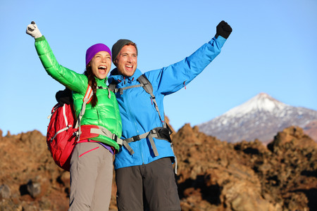 Happy celebrating winning hiking people at top. Cheering hiker couple enjoying freedom on hike with arms raised in mountain landscape. Woman and man on volcano Teide, Tenerife, Canary Islands, Spain photo