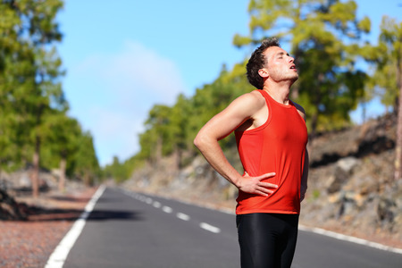 Runner rust moe en uitgeput na het lopen. Joggen man nemen van een pauze tijdens de training buiten in op bergweg. Jonge blanke man fitness model na het werk uit.