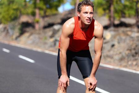 trabalhar fora: Corredor descansando ap�s a execu��o. Homem movimentando-se fazer uma pausa durante o treinamento ao ar livre em na estrada da montanha. Modelo caucasiano jovem macho de fitness depois do trabalho para fora.