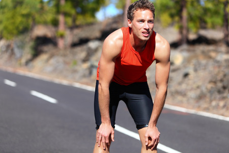 Runner resting after running. Jogging man taking a break during training outdoors in on mountain road. Young Caucasian male fitness model after work out. Stock Photo