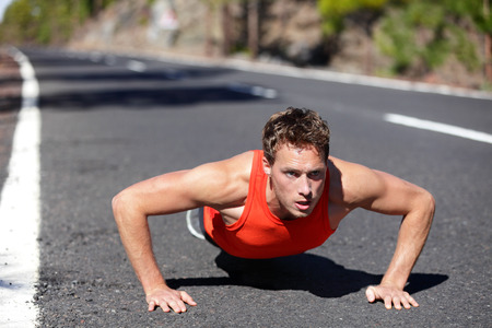 pushup: Push ups exercise man training pushup strength training outdoors. Fit muscular male fitness model warming up before running. Male runner in his 20s.