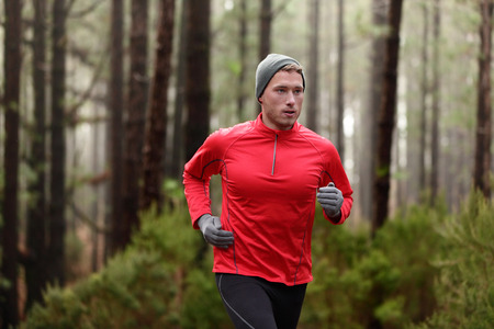 run: Running man in forest woods training and exercising for trail run marathon endurance race. Fitness healthy lifestyle concept with male athlete trail runner. Stock Photo