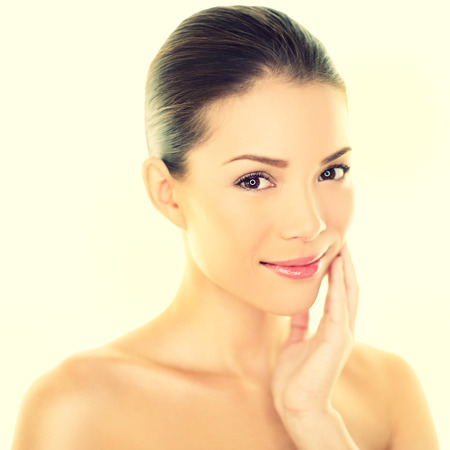 Woman beauty skincare woman touching perfect skin on face. Beautiful wellness beauty care and spa concept with multi-ethnic Chinese Asian  Caucasian girl with healthy glowing skin.
