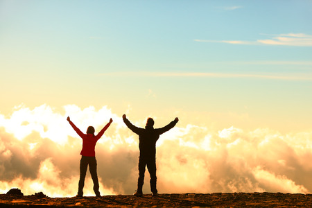 hiking people cheering and celebrating of joy with arms raised outstretched up in the sky photo