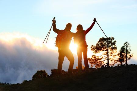 하이킹 사람들이 응원과 팔 기쁨의 축과 성공, 성취와 성취의 개념은 외부 하이킹 트레킹 위로 뻗은 발생합니다. 등산객 일몰 재미.