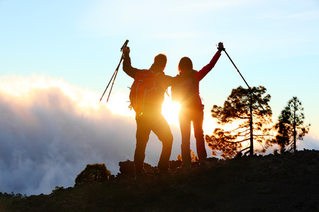 Success, achievement and accomplishment concept with hiking people cheering and celebrating of joy with arms raised outstretched up on trekking hike outside. Hikers having fun at sunset. photo