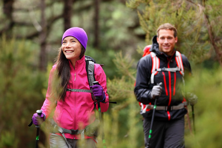 Hiking people - hikers trekking in forest on hike. Couple on adventure trek in beautiful forest nature. Multicultural Asian woman and Caucasian man living healthy active lifestyle in woods. photo