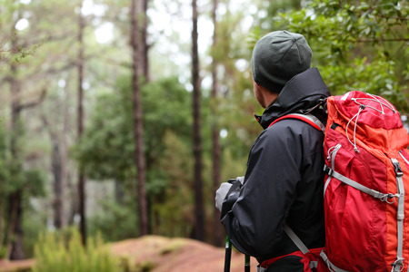 outdoor activities: Hiker wearing hiking backpack and hardshell jacket on hike in forest. Man wearing hat gloves using hiking sticks poles outdoors in woods. Male hiker standing looking away.