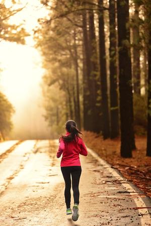 Atleet loopt op de weg in de ochtend zonsopgang training voor marathon en fitness. Gezonde actieve levensstijl vrouw uitoefening buitenshuis.