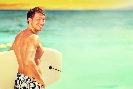 Surfer homme surfant sur la plage d'été. Homme bodyboard surf homme beau debout avec bodyboard planche de surf au cours escapade de vacances de vacances. Modèle sportif de l'eau du Caucase dans son 20s. Banque d'images
