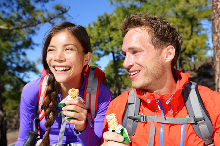 Couple eating muesli bar hiking. Happy people enjoying granola cereal bars living healthy active lifestyle in mountain nature. Woman and man hiker sitting laughing during hike.