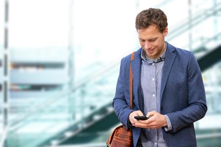 Young urban professional man met behulp van slimme telefoon in het kantoor gebouw binnen. Zakenman die mobiele smartphone met behulp van app sms sms-bericht dragen pak jas en tas. Stockfoto