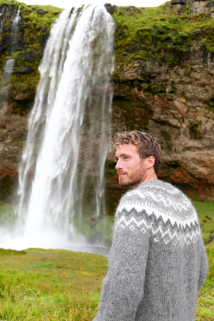 Man in Icelandic sweater by waterfall on Iceland outdoor smiling. Portrait of good looking male model looking to side in nature landscape with tourist attraction Seljalandsfoss waterfall on Ring Road. photo