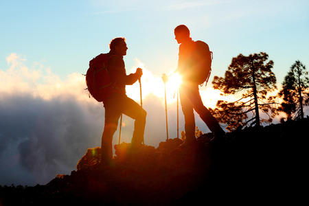 Hiking couple looking enjoying sunset view on hike during trek in mountain nature landscape at sunset. Active healthy couple doing outdoor activities.