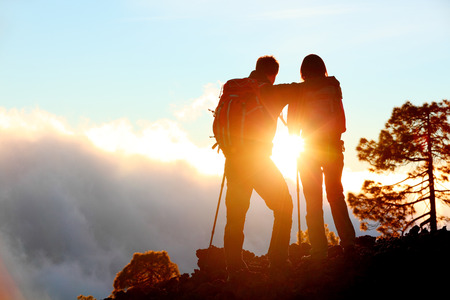 trekking pole: Hiking adventure healthy outdoors people standing talking. Couple enjoying sunset view above the clouds on trek. Video of young woman and man in nature wearing hiking backpacks and sticks.
