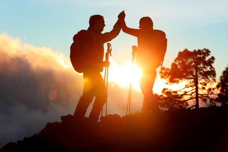 Hiking people reaching summit top giving high five at mountain top at sunset. Happy hiker couple silhouette. Success, achievement and accomplishment people