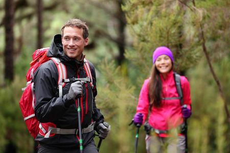 trekking pole: Hiking man and woman on hike in forest trekking. Couple on adventure trek in beautiful forest nature. Multicultural Asian woman and Caucasian man living healthy active lifestyle in woods. Stock Photo