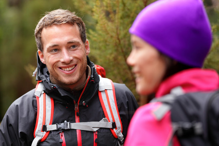 Male hiker portrait in forest talking with woman wearing backpack and jacket. Handsome man smiling candid during hike. Fresh male model in his 20s. photo