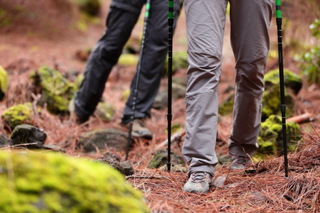 hiking stick: Hiking - Hikers walking in forest with hiking sticks on path trail in mountains. Close up of hiking shoes and boots. Man and woman hiking together.