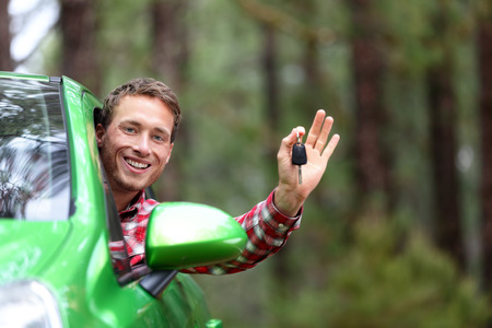 Car driver showing car keys and thumbs up happy. Young man holding car keys for new car. Rental cars or drivers licence concept with male driving in beautiful nature on road trip. Standard-Bild
