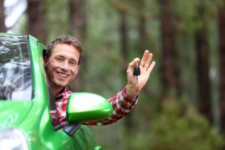 Automobilist tonen autosleutels en duimen omhoog gelukkig. Jonge man die autosleutels voor nieuwe auto. Huurauto's of rijbewijs concept met mannelijke rijden in de prachtige natuur op road trip. Stockfoto
