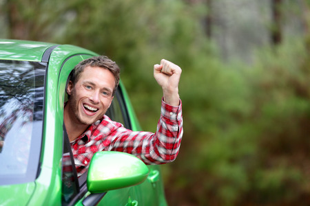 Green energy biofuel electric car driver happy and excited. Man driving new vehicle in cheerful in nature forest. Young male driver looking at camera with arm raised cheering. Stock Photo