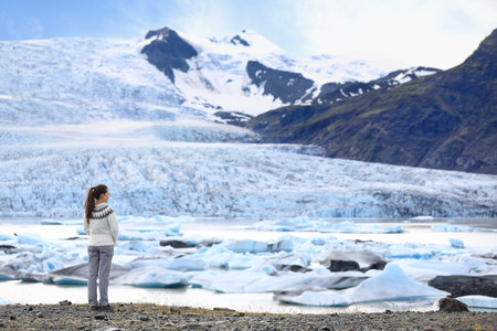 fjallsarlon: Adventure woman by glacier nature on Iceland. Tourist in Icelandic sweater by glacial lagoon  lake of Fjallsarlon, Vatna glacier, Vatnajokull National Park. Young woman visiting nature landscape.