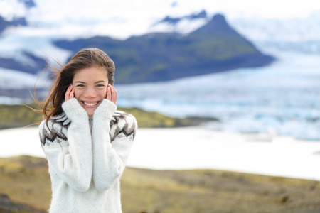 fjallsarlon: Asian woman portrait by glacier on Iceland wearing Icelandic sweater. Hiker tourist girl smiling cute in nature by glacial lagoon  lake of Fjallsarlon, Vatna glacier, Vatnajokull National Park.
