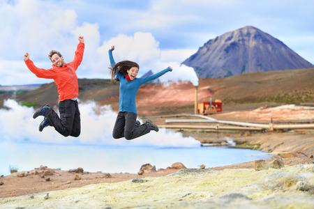 IJsland reizen mensen springen van vreugde in de voorkant van de hete lente en geothermische energiecentrale in Námafjall in het Myvatn gebied. Gelukkig paar op reizen in de natuur in IJsland landschap, Route 1 Ring Road.