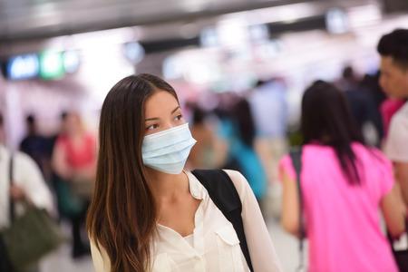 surgical: Persona con máscara protectora contra las enfermedades infecciosas transmisibles y como protección contra la contaminación y la gripe. Viajero de la mujer asiática en el aeropuerto de la zona pública. Foto de archivo