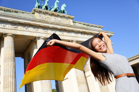 German flag - Woman happy at Berlin Brandenburg Gate cheering celebrating waving flag by Brandenburger Tor, Germany. Cheerful excited multiracial woman in Germany travel concept. Stock Photo