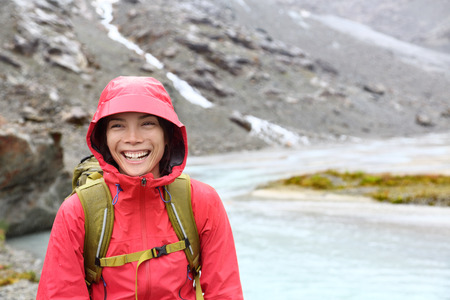 Hiker woman hiking with backpack in rain on trek living healthy active lifestyle. Smiling cheerful girl walking on hike in beautiful mountain nature landscape while raining in Swiss alps, Switzerland. photo