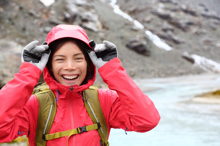 Laughing happy woman hiking with backpack in rain on trek living healthy active lifestyle. Smiling cheerful girl walking on hike in beautiful mountain nature landscape raining, Swiss alps, Switzerland photo