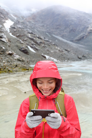 conductive: Smart phone woman texting sms using app on smartphone with touchscreen gloves. Happy hiker with mobile phone outside in nature in rain. Girl with glove of conductive fabric for touch screen. Stock Photo