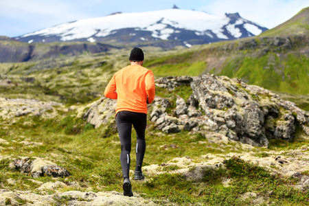 ultra: Sport athlete - exercising trail runner running. Active male fitness model training and jogging outdoors in beautiful mountain nature landscape by Snaefellsjokull, Snaefellsnes, Iceland.