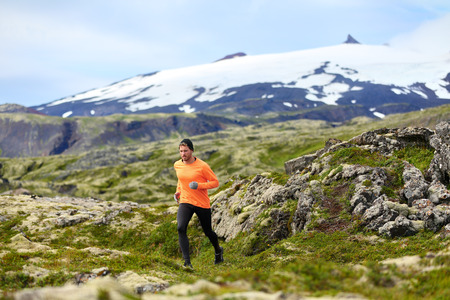 iceland: Running man athlete exercising trail runner. Fit male sport fitness model training and jogging outdoors in beautiful mountain nature landscape by Snaefellsjokull, Snaefellsnes, Iceland. Stock Photo