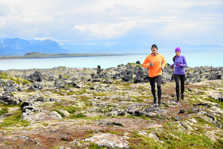 Exercise running sport. Runners on cross country trail run outdoors working out. Fit young fitness model man and asian woman training together outside in mountain nature on Snaefellsnes, Iceland. Stock Photo