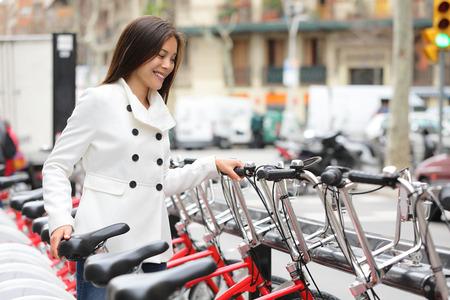 シティ自転車 - 都市公共自転車共有システムを使用して女性。女性専門の都市の自転車でサイクリング後シティー バイク駐車場自転車に乗る。バル