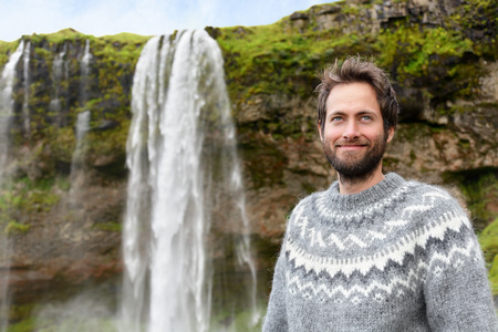 scandinavian people: Man in Icelandic sweater by waterfall on Iceland. Bearded male portrait of good looking guy in his 30s in nature landscape with tourist attraction Seljalandsfoss waterfall on Ring Road.