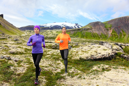Sport running. Runners on cross country trail outdoors working out for marathon. Fit young fitness model man and asian woman training together outside in mountain nature on Snaefellsnes, Iceland. photo