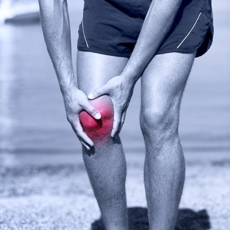 sprained joint: Knee Injury - sports running knee injuries on man. Male runner with pain from sprain knee. Close up of legs, muscle and knee outdoors.