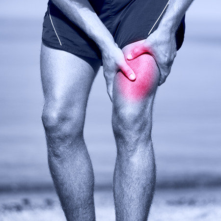 physical injury: Muscle sports injury of male runner thigh. Running muscle strain injury in thigh. Closeup of runner touching leg in muscle pain.