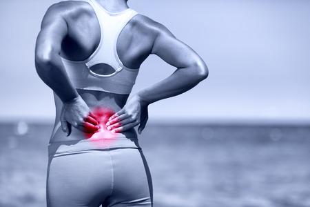 Back pain. Athletic running woman with back injury in sportswear rubbing touching lower back muscles standing on road outside. Stock Photo