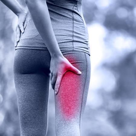 muslos: Esguince de tendón de la corva o calambres. Ejecución de una lesión deportiva con corredora. Primer de la cara posterior del muslo mujer.