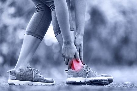 pies: Broken tobillo torcido - Ejecuci�n de una lesi�n deportiva. Mujer corredor de sus pies tocando en el dolor debido a la lesi�n en el tobillo.