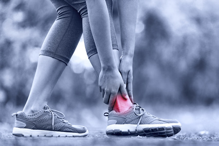 Broken twisted ankle - running sport injury. Female runner touching foot in pain due to sprained ankle.