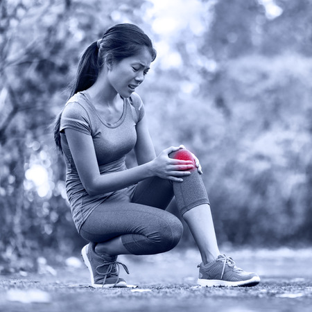 aching muscles: Knee Injury - sports running knee injuries on woman in pain. Female runner with pain from sprain knee. Close up of legs, muscle and knee outdoors.